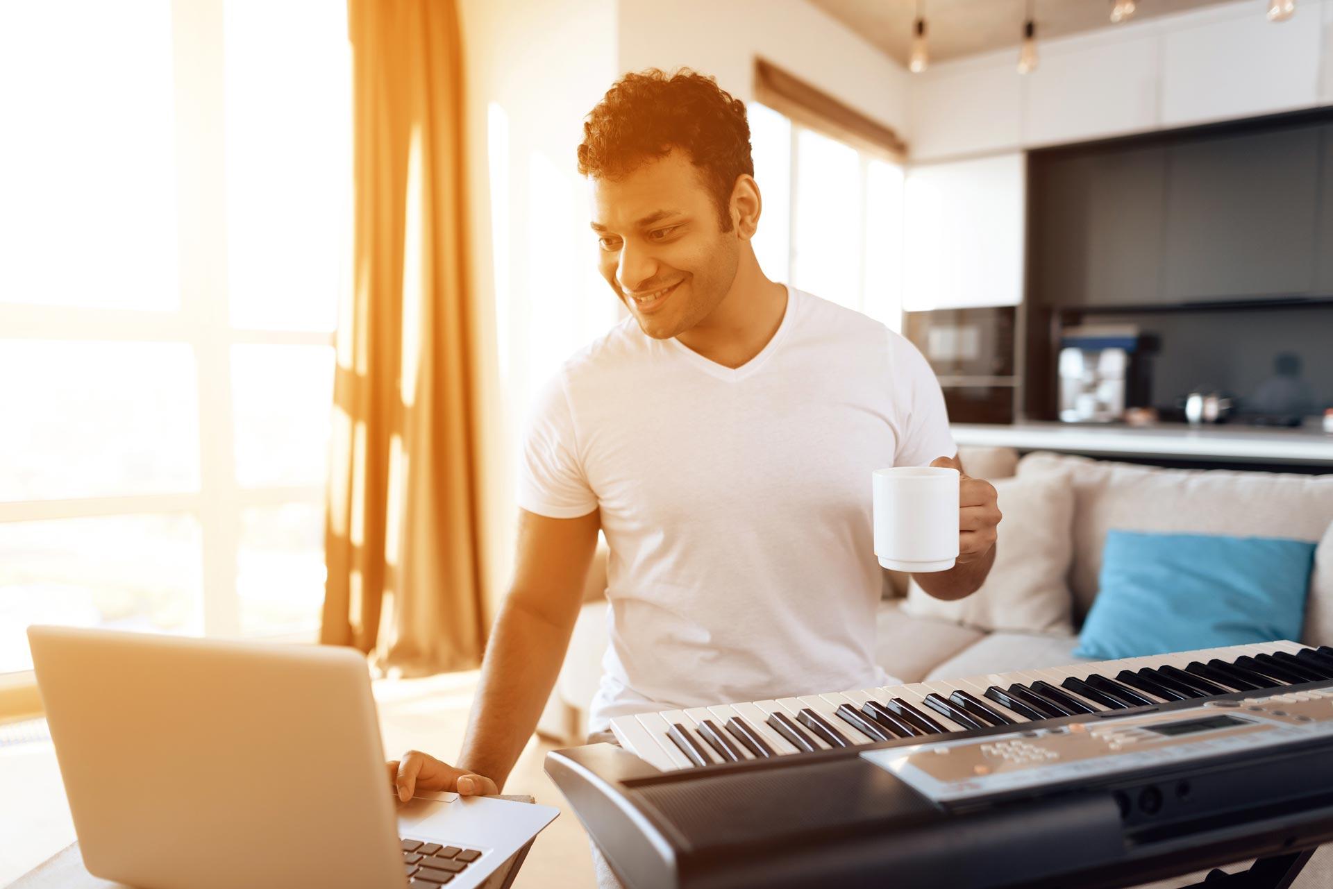 Volwassen man die keyboard en computer speelt